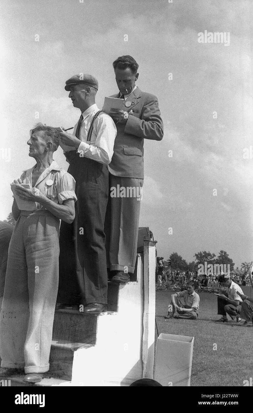 Degli anni Cinquanta, storico, tre cronometristi maschio su un elevato di cronometraggio in legno stand rendere Immagini Stock