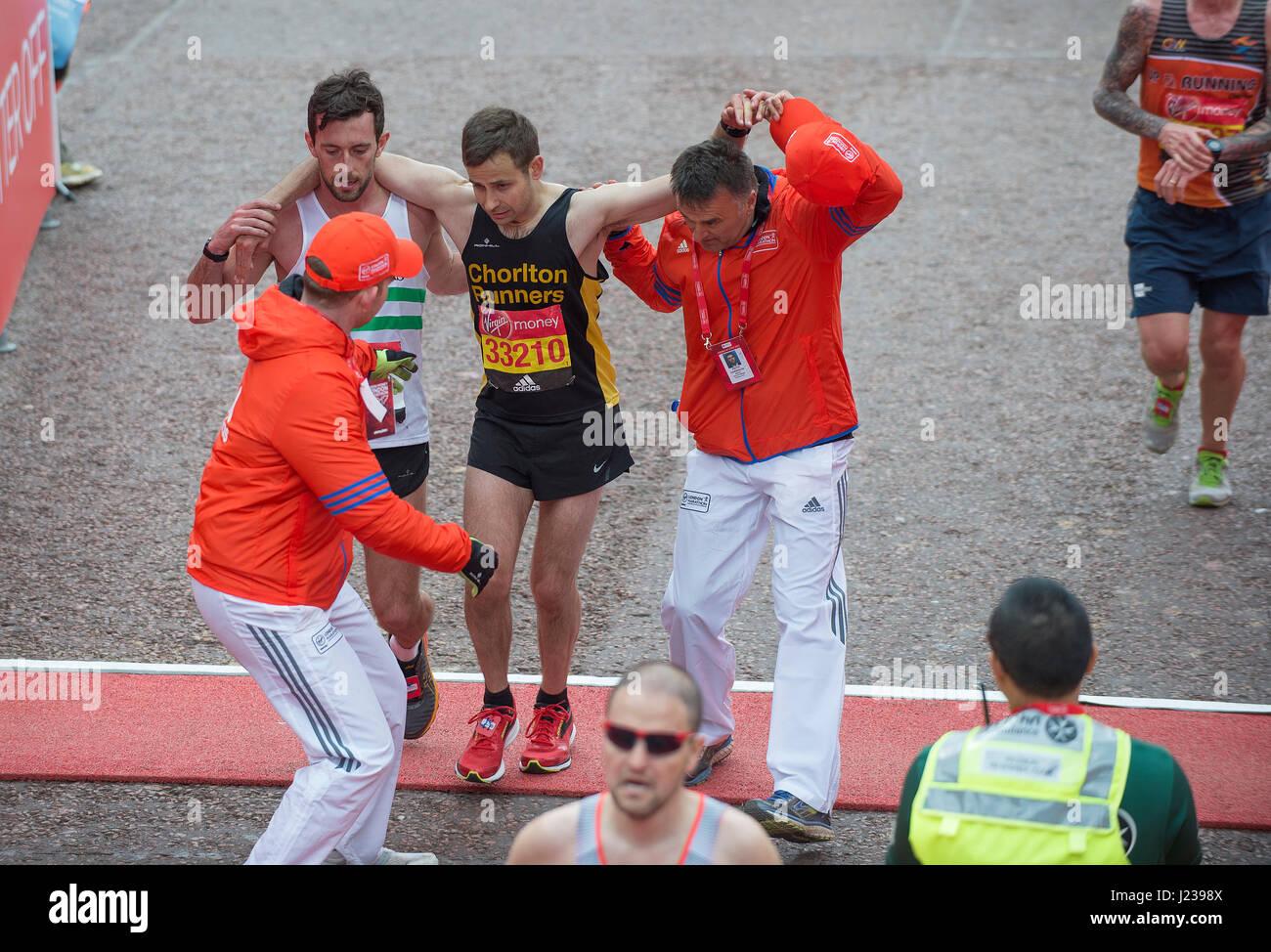 Guida per un runner attraversando il traguardo con gambe di gelatina, 2017 denaro Virgin London Marathon. Credito: Immagini Stock