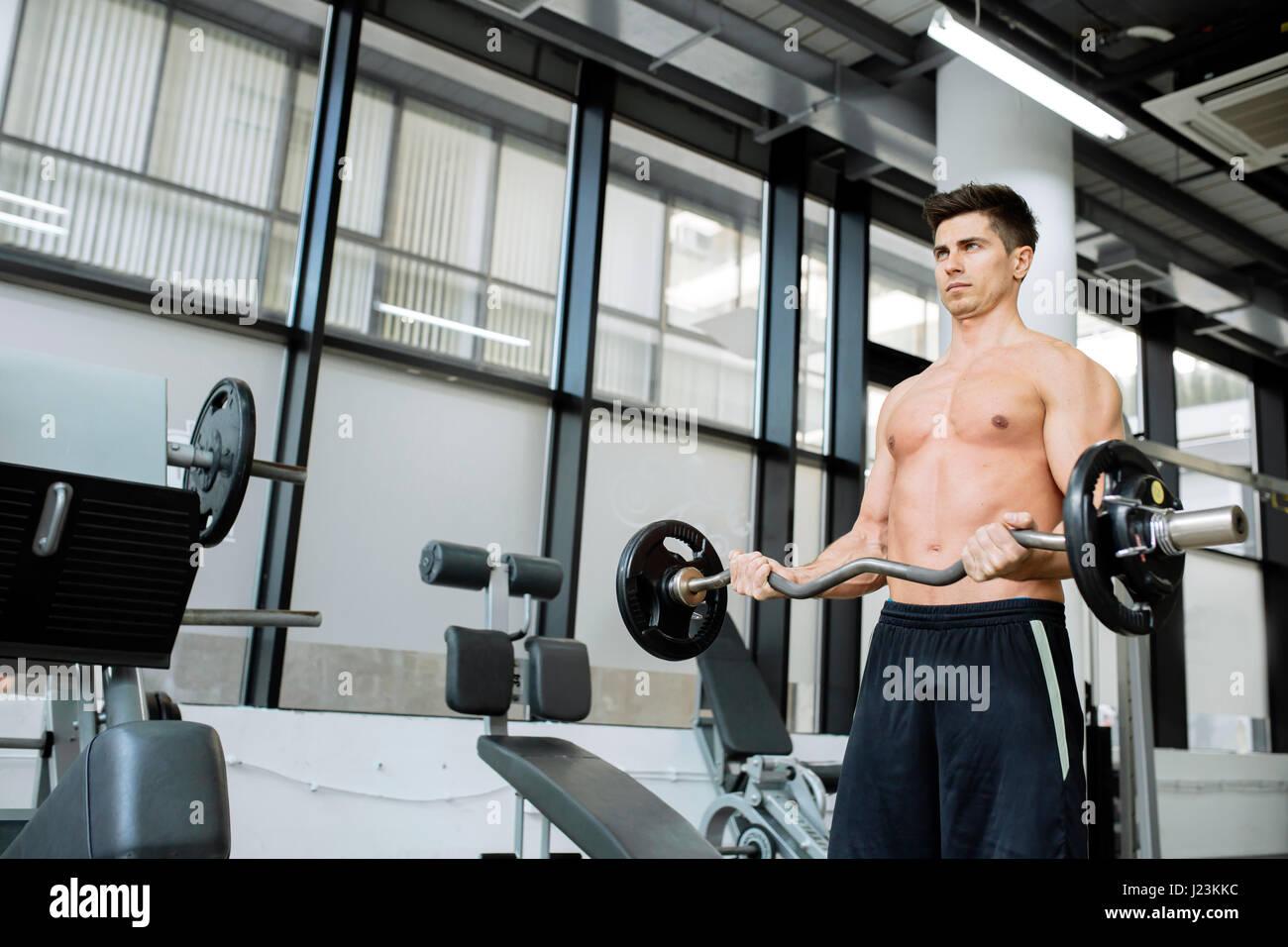 Uomo muscolare bodybuilding in palestra, sollevamento pesi Immagini Stock