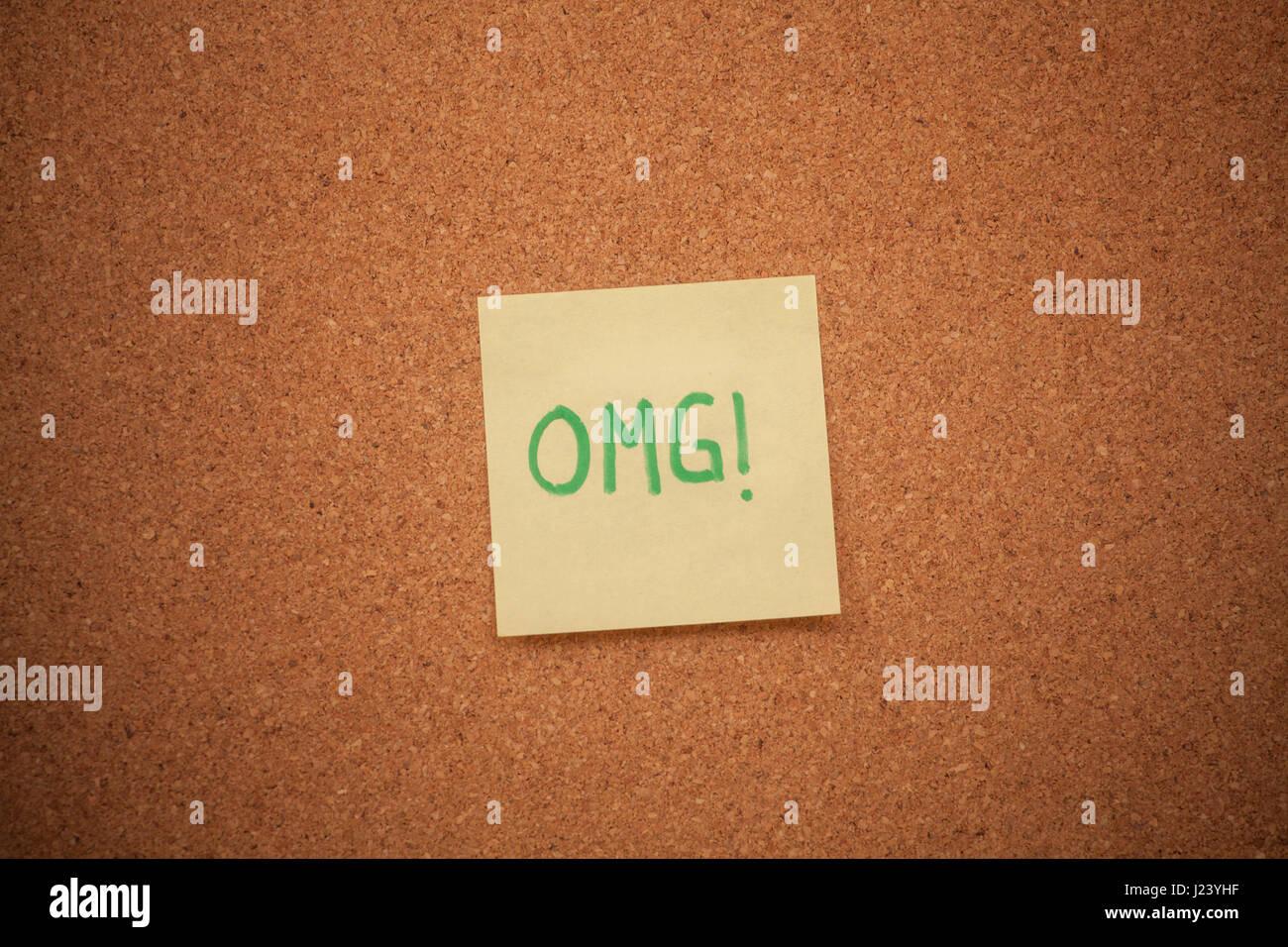 Immagine ravvicinata di una nota di lettura OMG bloccati su una bacheca di sughero. Foto Stock