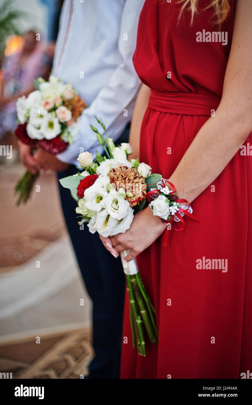 super popular a878c 9cc9c Mani di damigelle in abiti rosso con bouquet di matrimonio ...