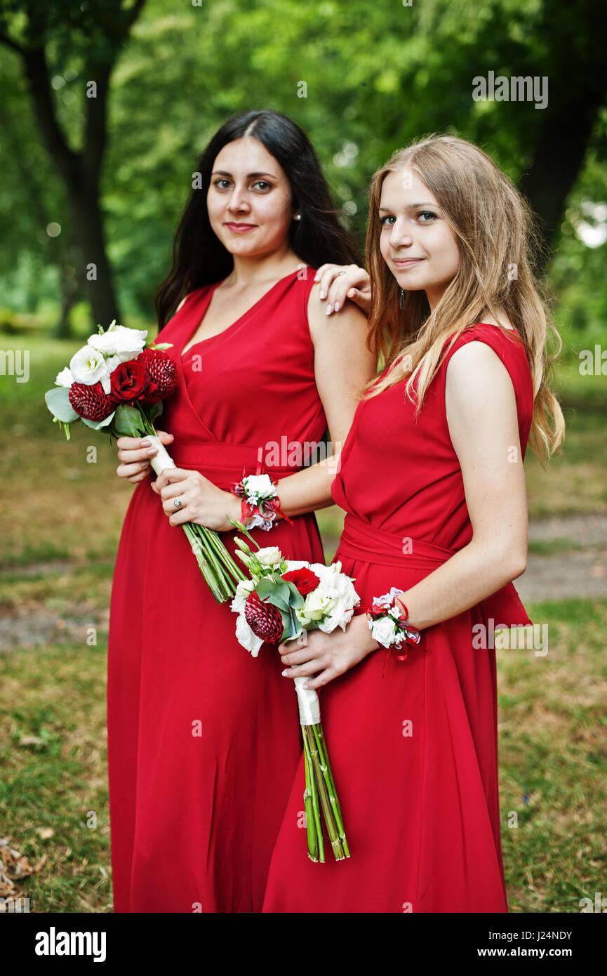 best service 691ff e7b85 Due ragazze damigelle in abiti rossi con mazzi di fiori per ...