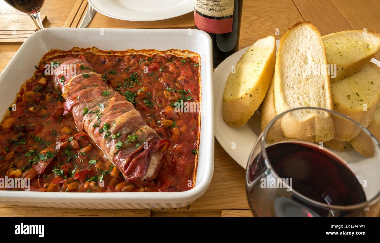 Close up italiane di filetti di maiale su letto di pomodori, fagioli e aglio con la piastra di aglio pane, un bicchiere Immagini Stock