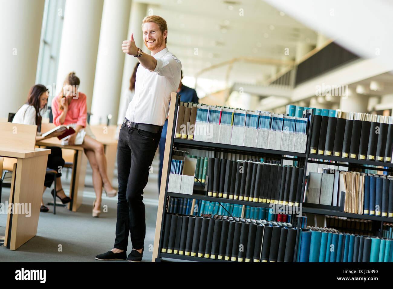 Un gruppo di giovani che studiano la lettura e l'istruzione se stessi nella libreria Immagini Stock