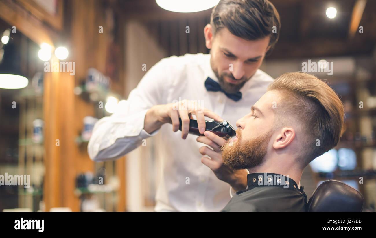 Giovane uomo nel negozio di Barbiere per la cura dei capelli il concetto di servizio Immagini Stock