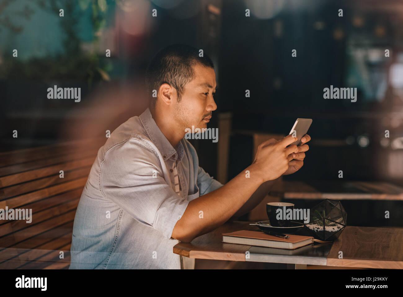 Giovani asiatici uomo seduto in un bar di navigare su internet Immagini Stock