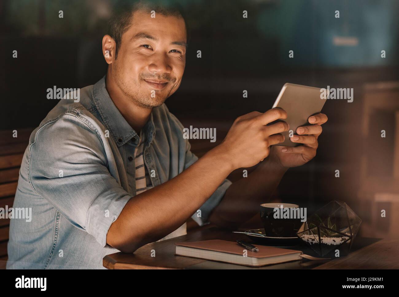 Contenuto uomo asiatico navigazione online mentre è seduto in un bar Immagini Stock
