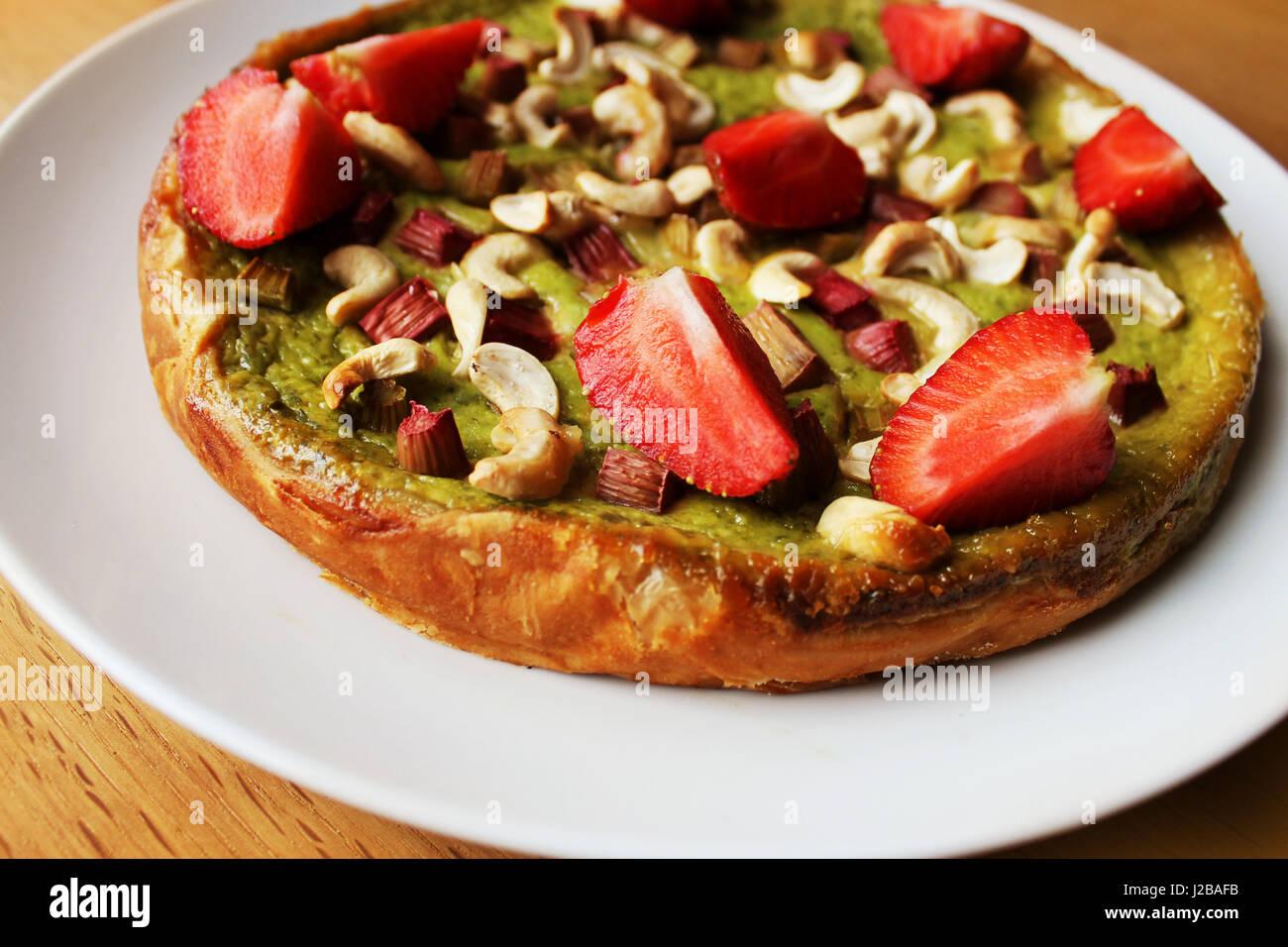 Tè verde Matcha torta con fragole e rabarbaro, noci di acagiù Immagini Stock