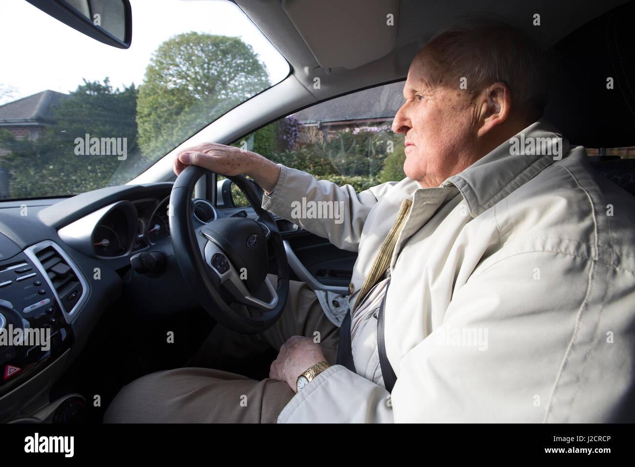 Uomo anziano nei suoi anni ottanta alla guida di una vettura, England, Regno Unito Immagini Stock