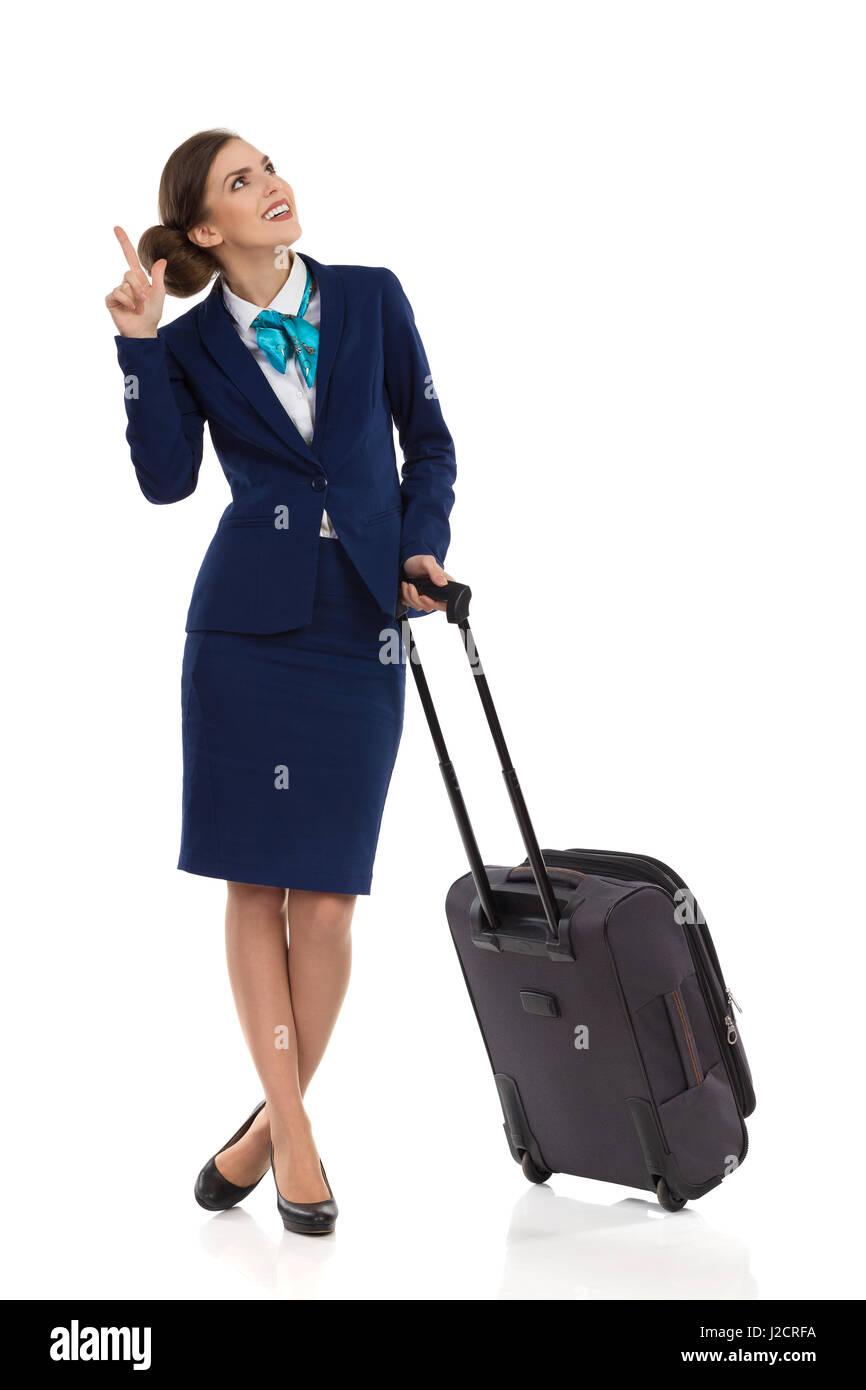 Donna sorridente in formale tuta blu e mantello in piedi con la valigia trolley, guardando verso l'alto e puntamento. Immagini Stock