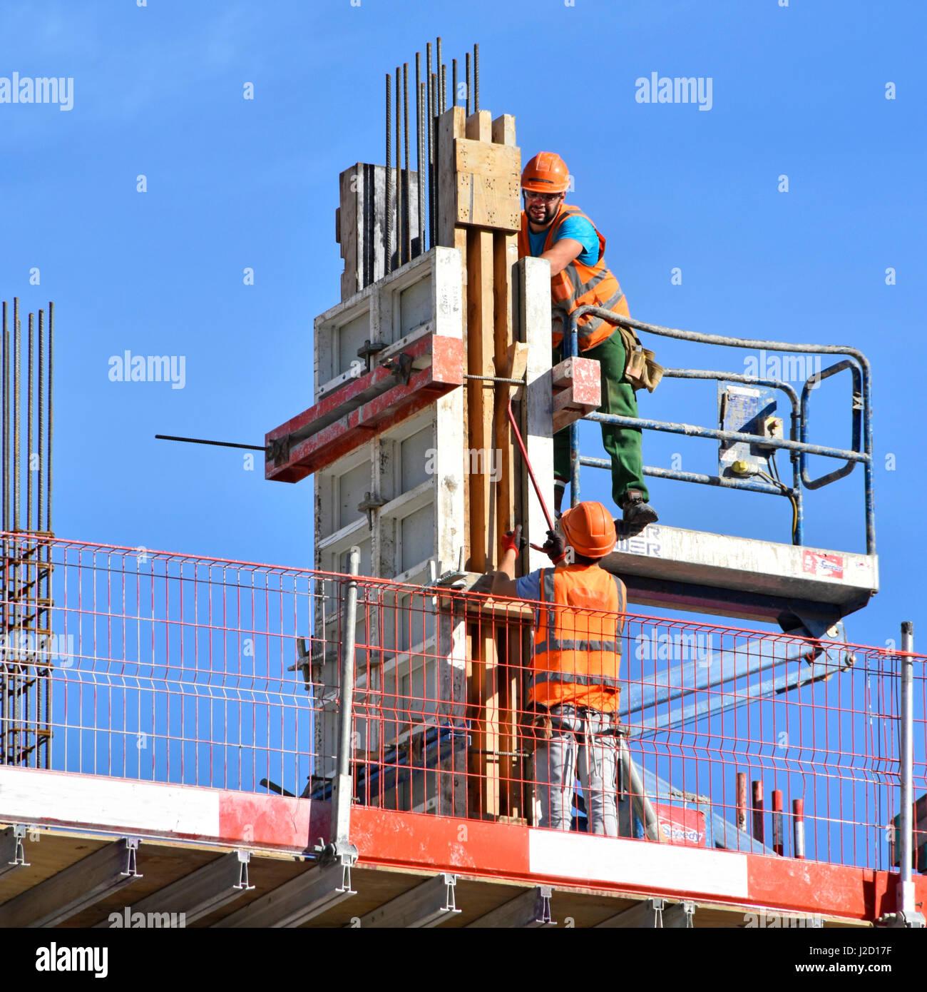 Salute & Sicurezza edificio uk cantiere lavoratore colonna fissaggio cassero lavoratori Indossare copricapi Immagini Stock