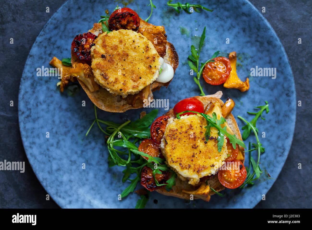 Cotto formaggi di capra su pane a lievitazione naturale con finferli e pomodorini Immagini Stock