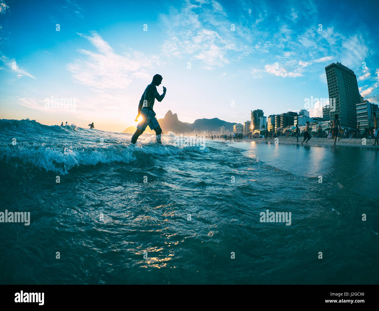RIO DE JANEIRO - Febbraio 2, 2013: un giovane brasiliano passeggiate attraverso le onde sulla riva della spiaggia Immagini Stock
