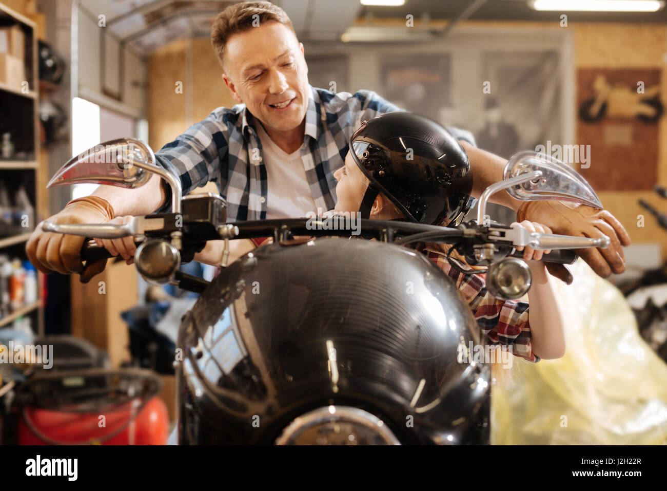 Avventuroso famiglia incantevole fingendo di essere in sella a una moto Immagini Stock