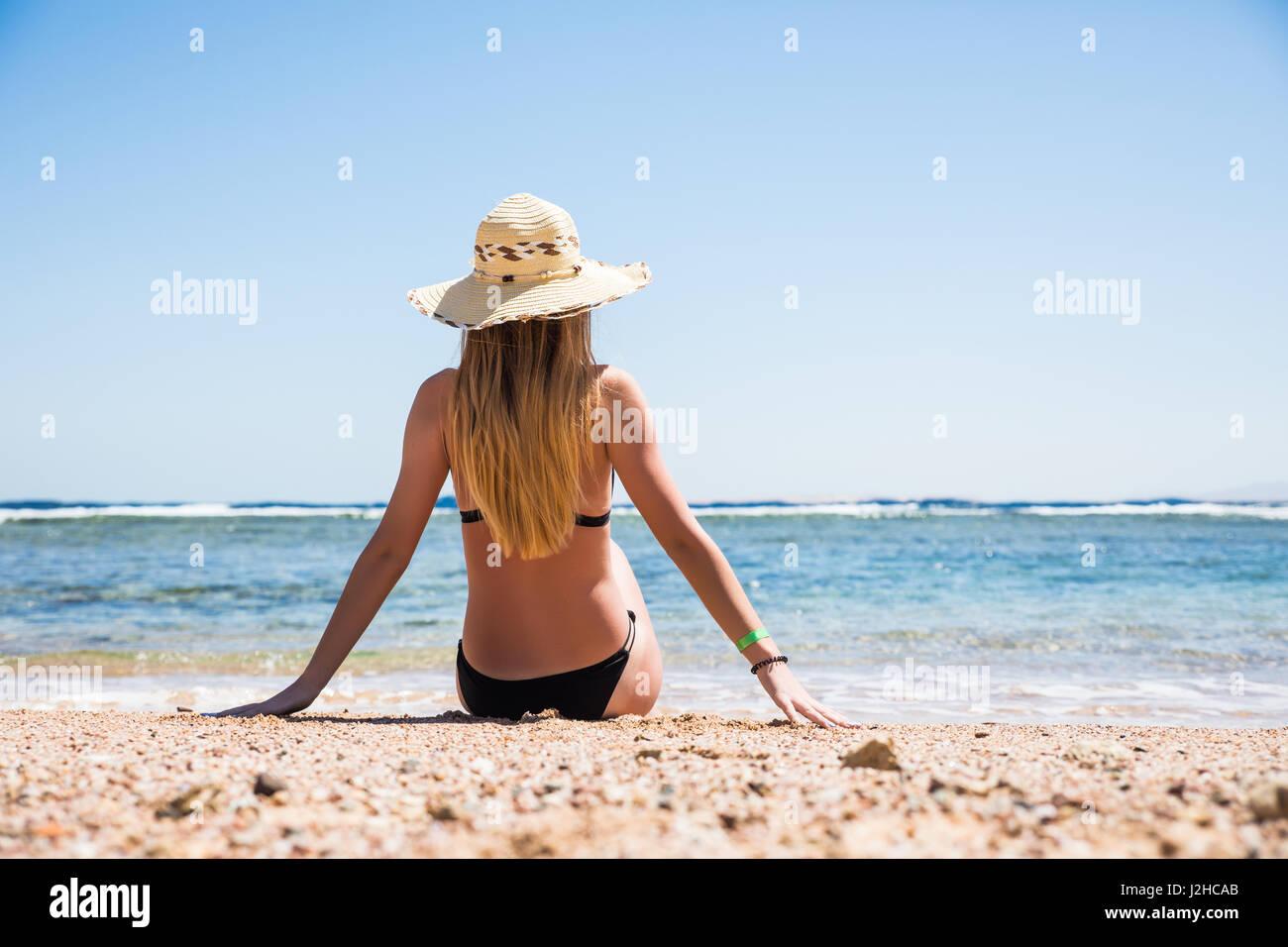 Donna in bikini bianco in appoggio sulla spiaggia nel cappello di paglia  Immagini Stock a41424b858ff