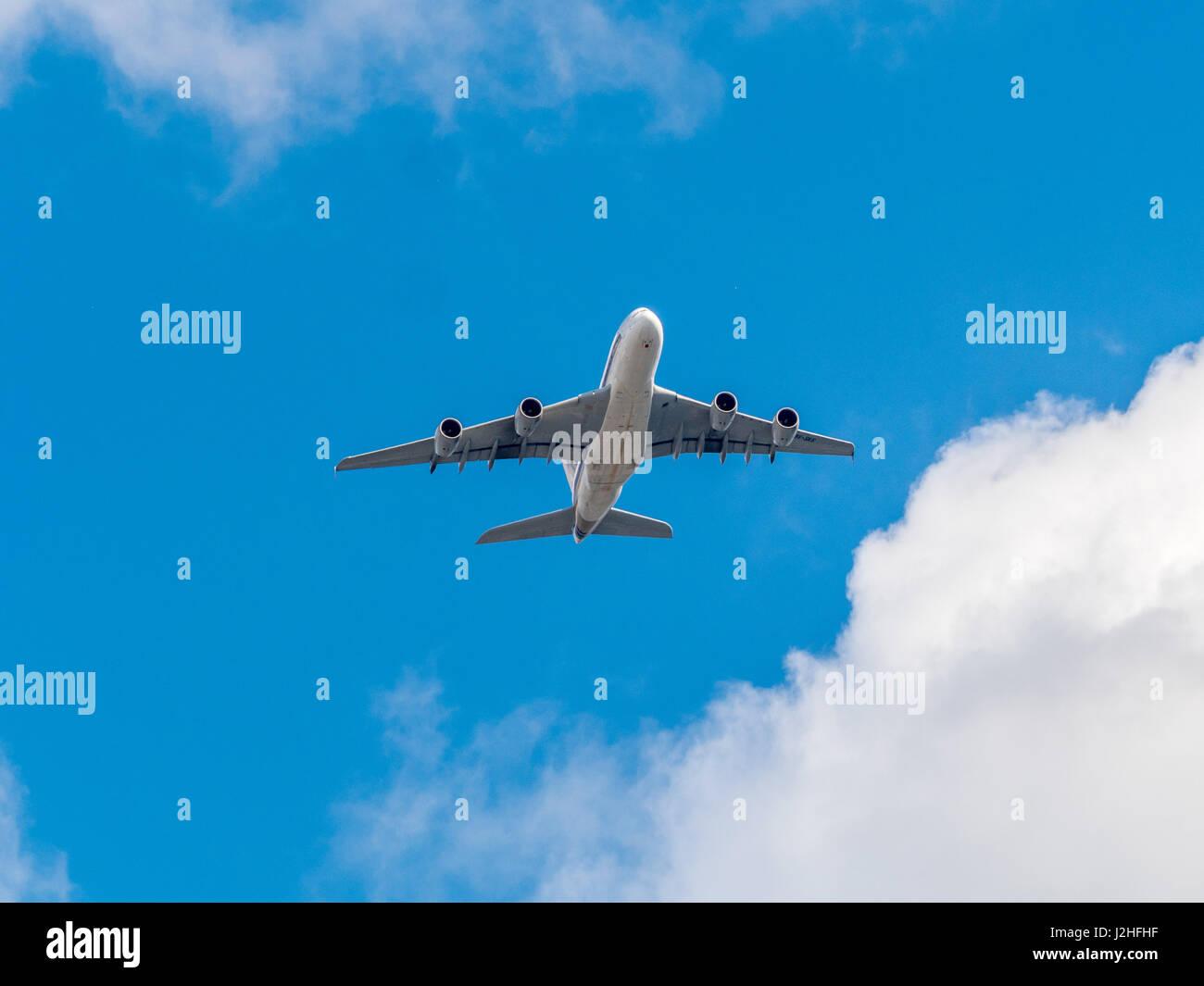 Passeggeri a getto piano contro il cielo blu con nuvole visto dal di sotto. Immagini Stock