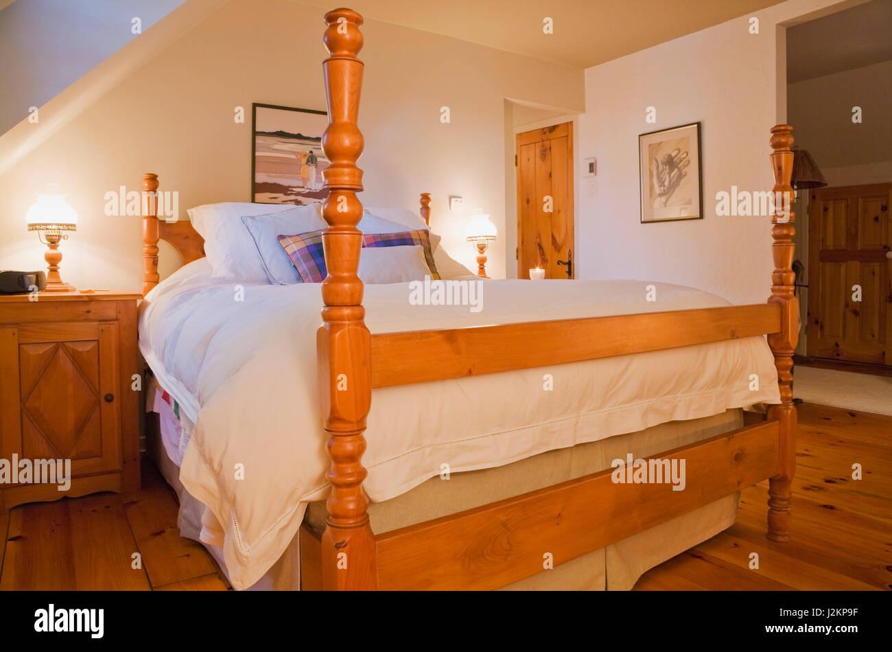 Letto queen size sul telaio di legno con alte bedposts nella