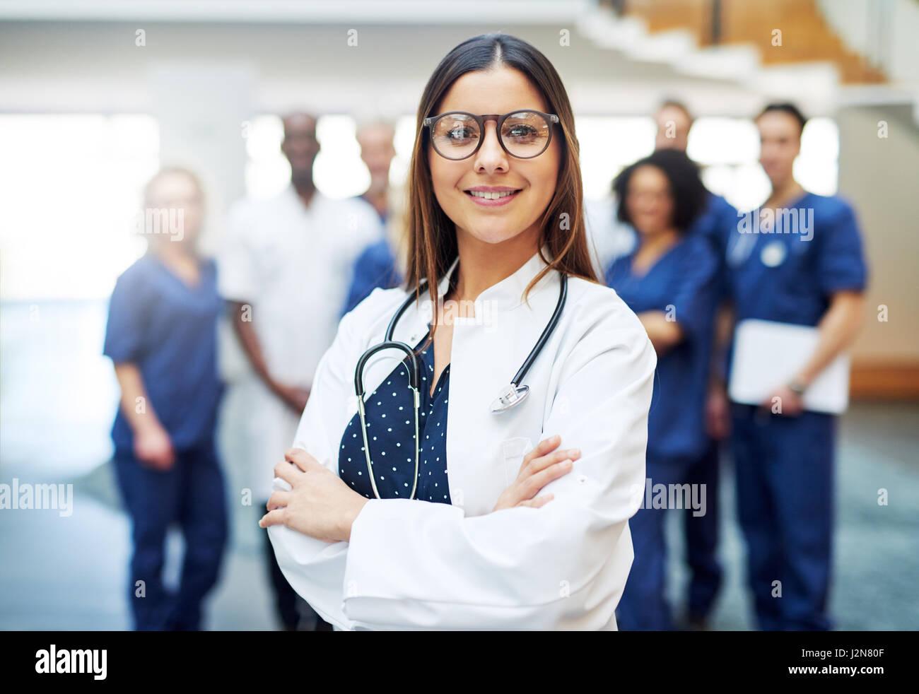 Multirazziale medico donna in piedi nella parte anteriore del team medico in ospedale. Guardando la fotocamera e Foto Stock