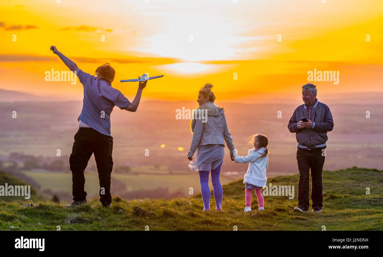Famiglia amorevole giocando e gustando ottimi tempi su una collina vicino al tramonto nella campagna del Regno Unito. Trascorrere del tempo insieme. Foto Stock