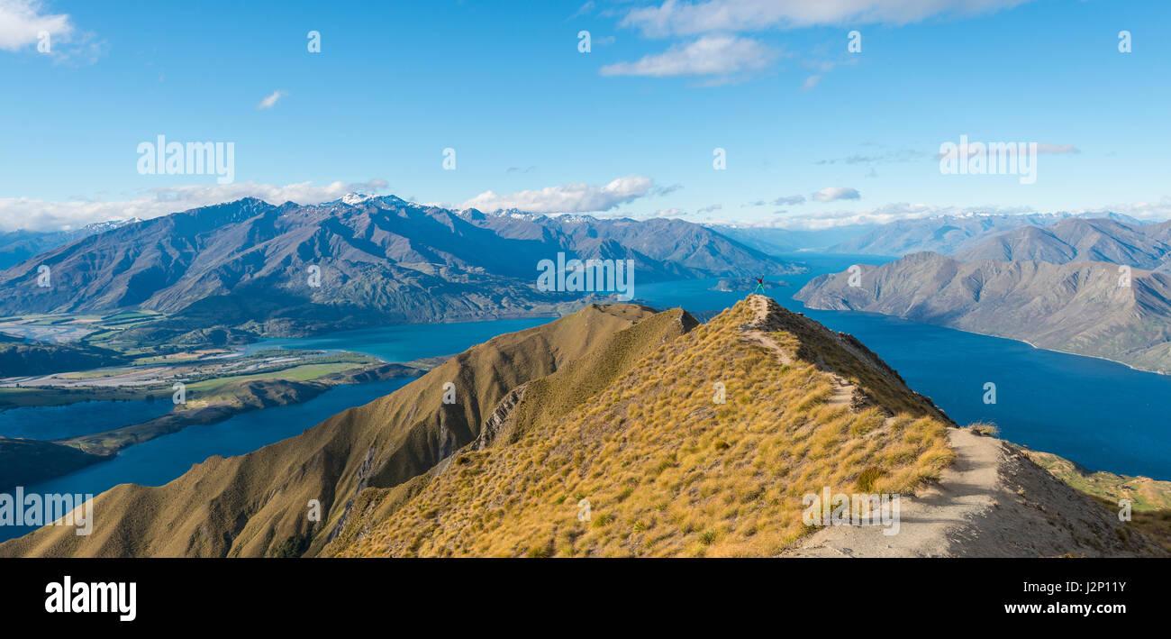 Vista sulle montagne e sul lago, donna salta in alto crinale, Roys picco, il lago Wanaka, Alpi del Sud, regione Immagini Stock