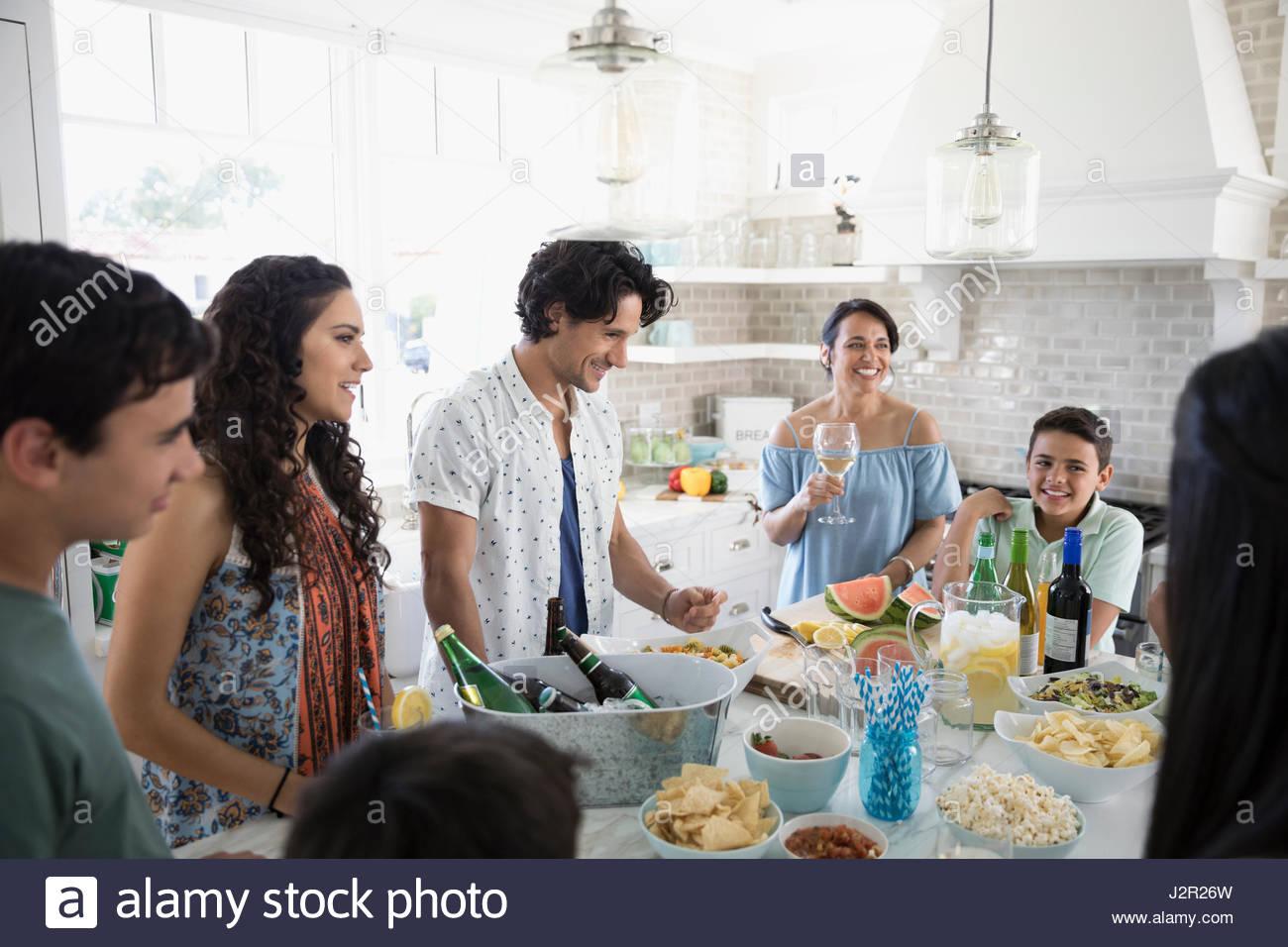 La famiglia e gli amici a bere e mangiare nella casa sulla spiaggia cucina Immagini Stock