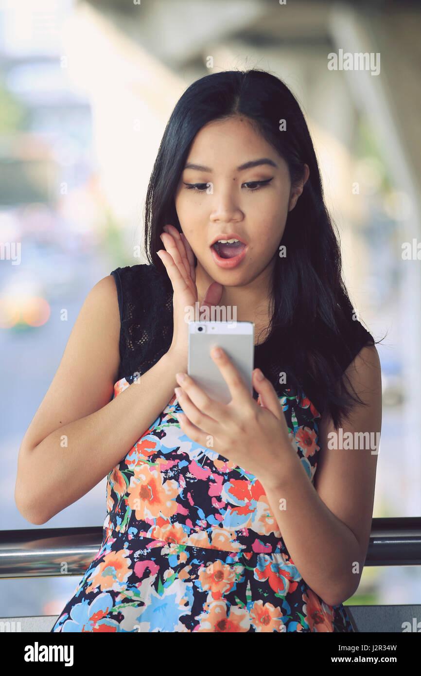 Donna asiatica guardando sorpreso per il suo telefono cellulare Immagini Stock