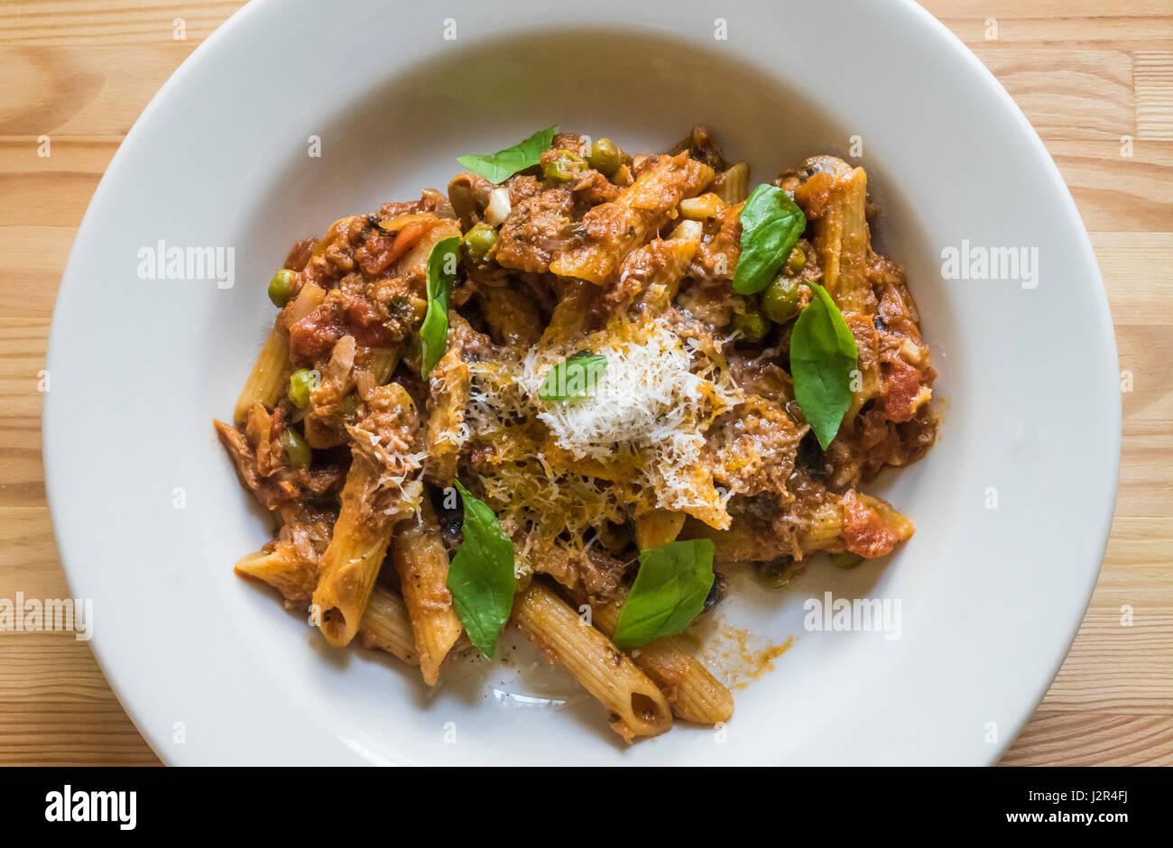 Penne pasta con pollo e funghi, piselli verdi, basilico e pomodori Immagini Stock