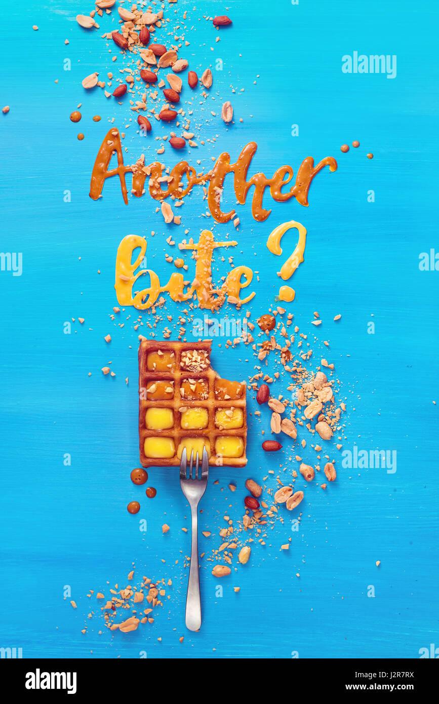 Una forcella con i waffle belgi su un cielo blu sullo sfondo di legno con le parole di un altro morso realizzato Immagini Stock