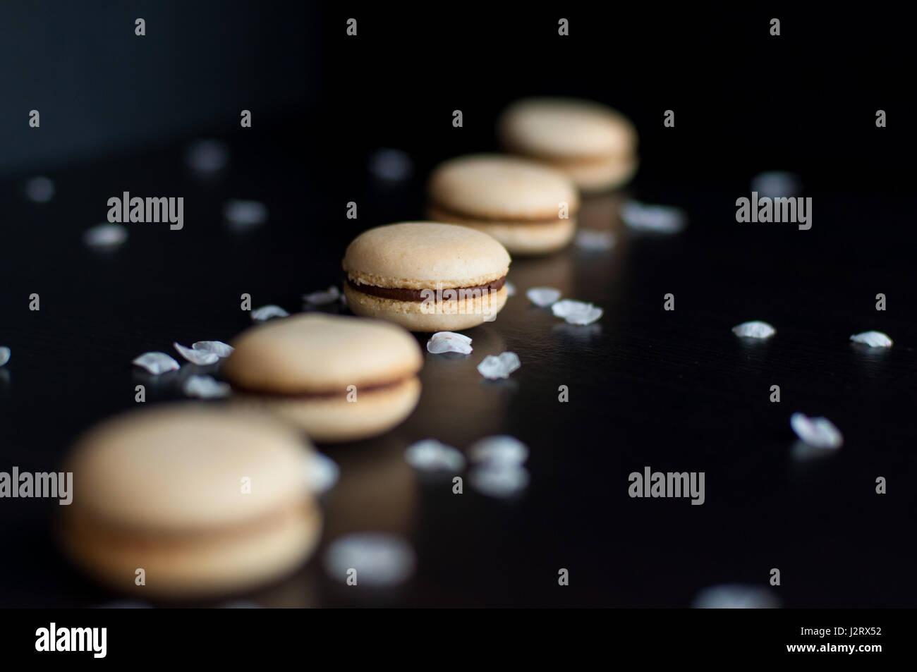 Amaretti con crema di cioccolato ordinati in linea decorato con ciottoli e sabbia Immagini Stock
