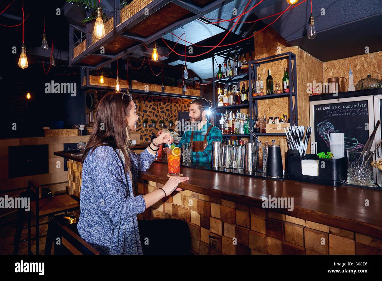 Una ragazza con cocktail di sorrisi dietro il contatore al bar Immagini Stock