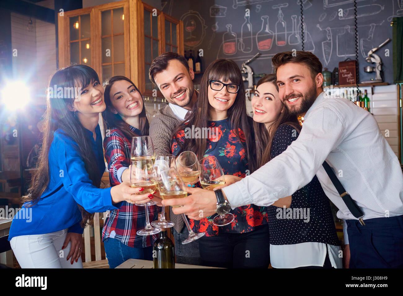 Gli amici con gli occhiali alla celebrazione nel ristorante divertirsi un Immagini Stock