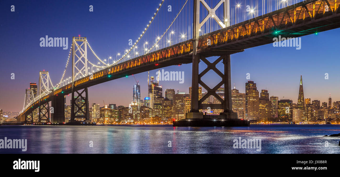 Classic vista panoramica del famoso Oakland Bay Bridge con lo skyline di San Francisco illuminata nella splendida Immagini Stock