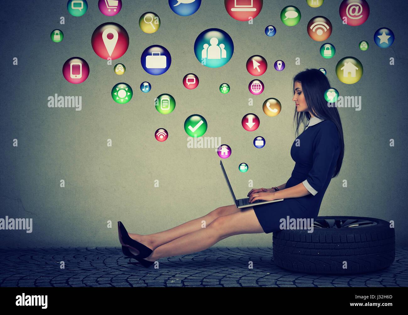 Giovane donna seduta su un pneumatico lavora su un computer portatile con i social media le icone delle applicazioni Immagini Stock