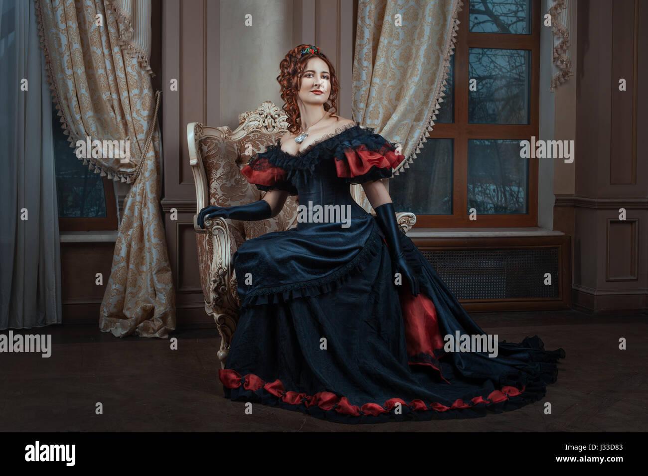 Donna in abito vittoriano seduto su una sedia in camera. Foto Stock