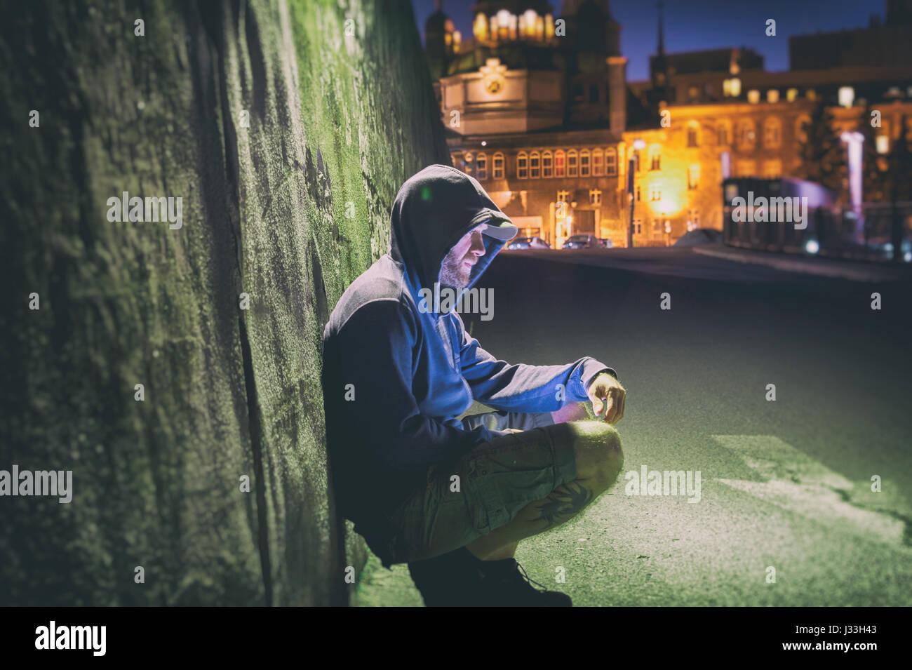 Triste e uomo solitario con hoodie seduto contro un muro di notte Immagini Stock