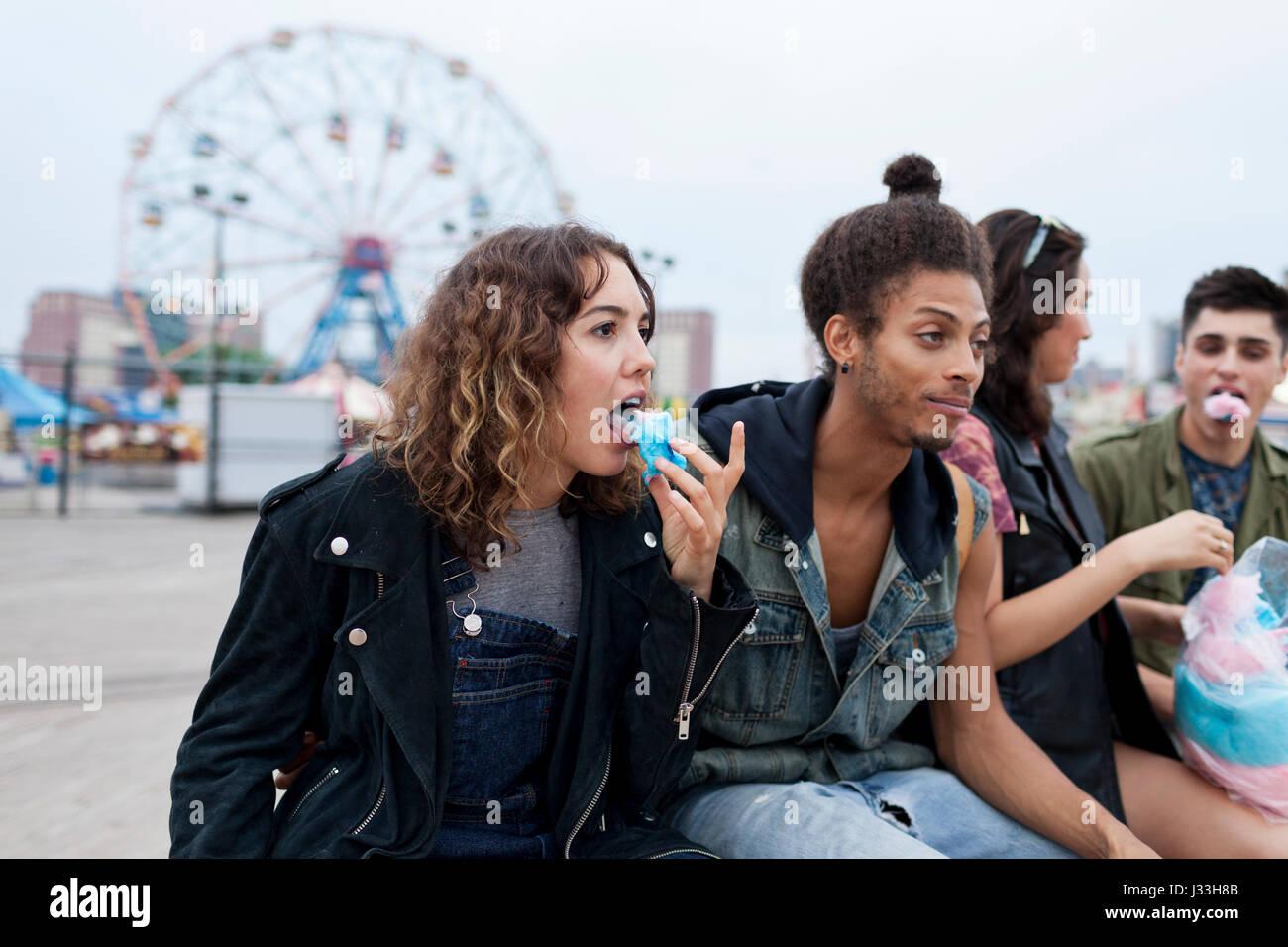 Gli amici di mangiare la caramella di cotone in un parco di divertimenti Immagini Stock