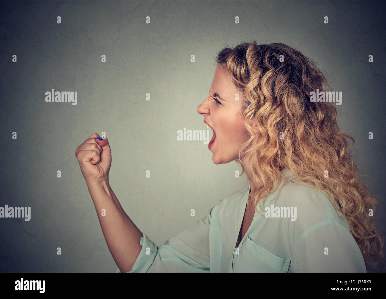 Arrabbiato donna urlare con pugno fino in aria Immagini Stock