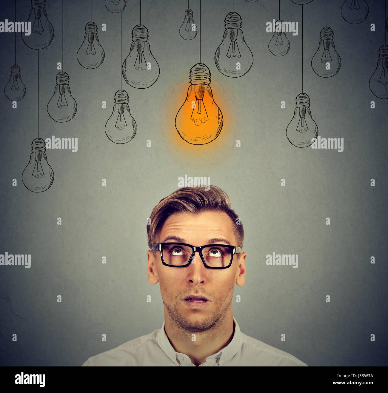 Considerato l uomo in bicchieri cercando con luce idea segno della lampadina sopra la testa ha un'idea isolata Immagini Stock