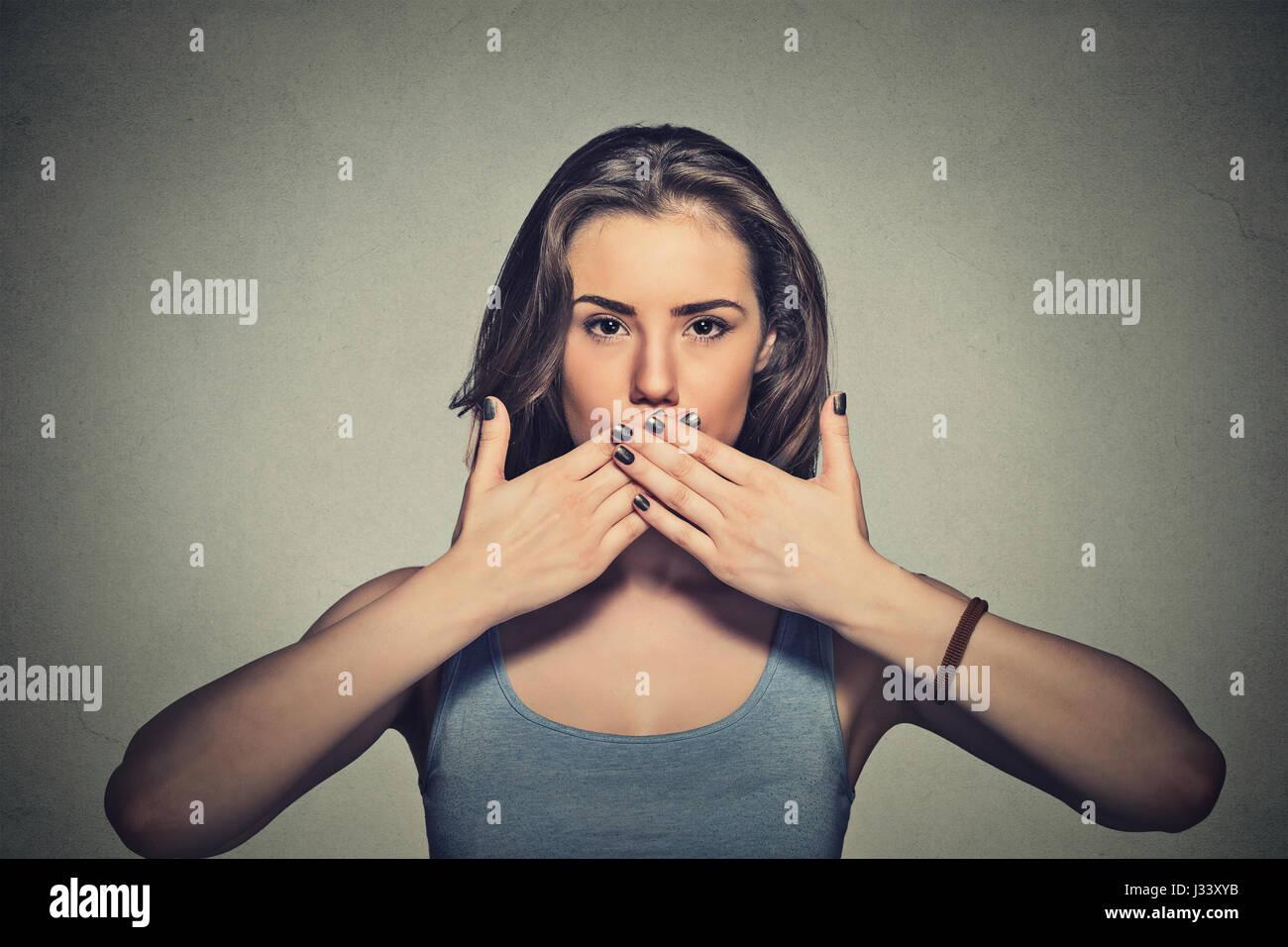 Closeup Ritratto di giovane donna la copertura con le mani la sua bocca isolato sul muro grigio sfondo Foto Stock