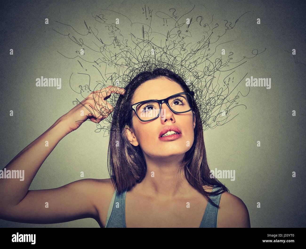Closeup ritratto giovane donna di graffiare la testa, pensando fantasticando con fusione del cervello in linee interrogativi Immagini Stock