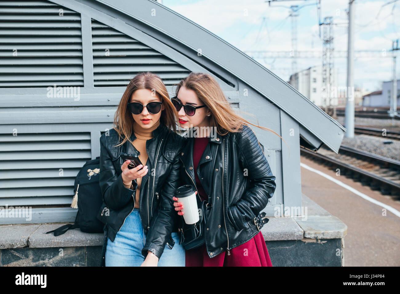 Conversazione tra due donne nella città.Outdoor Lifestyle ritratto di due migliori amici hipster ragazze indossano Elegante giacca di pelle e occhiali da sole con caffè, going crazy e avente un grande tempo insieme Foto Stock