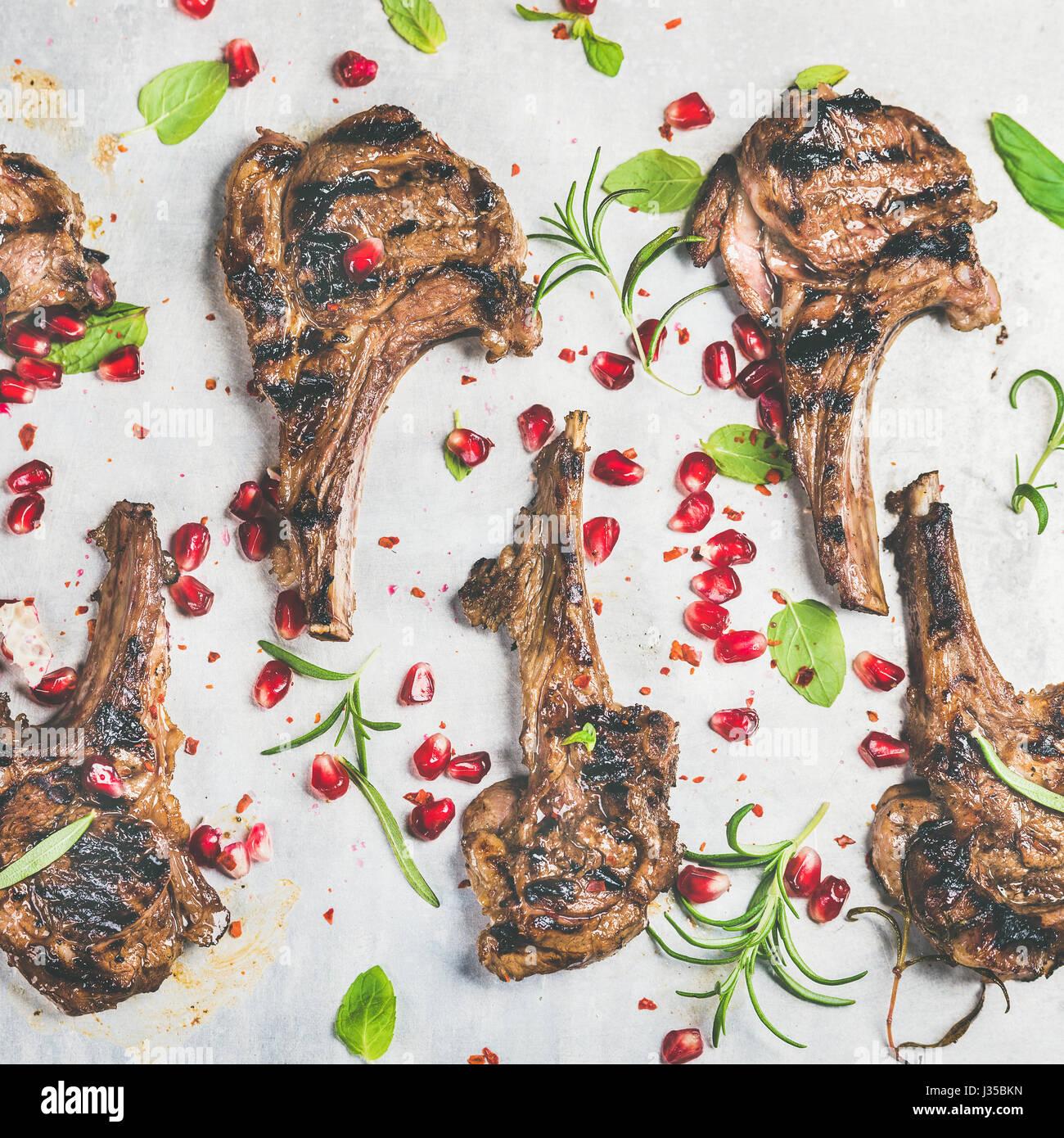 Slow food la Cena con grigliata di costolette di agnello e melograno, erbe aromatiche Immagini Stock