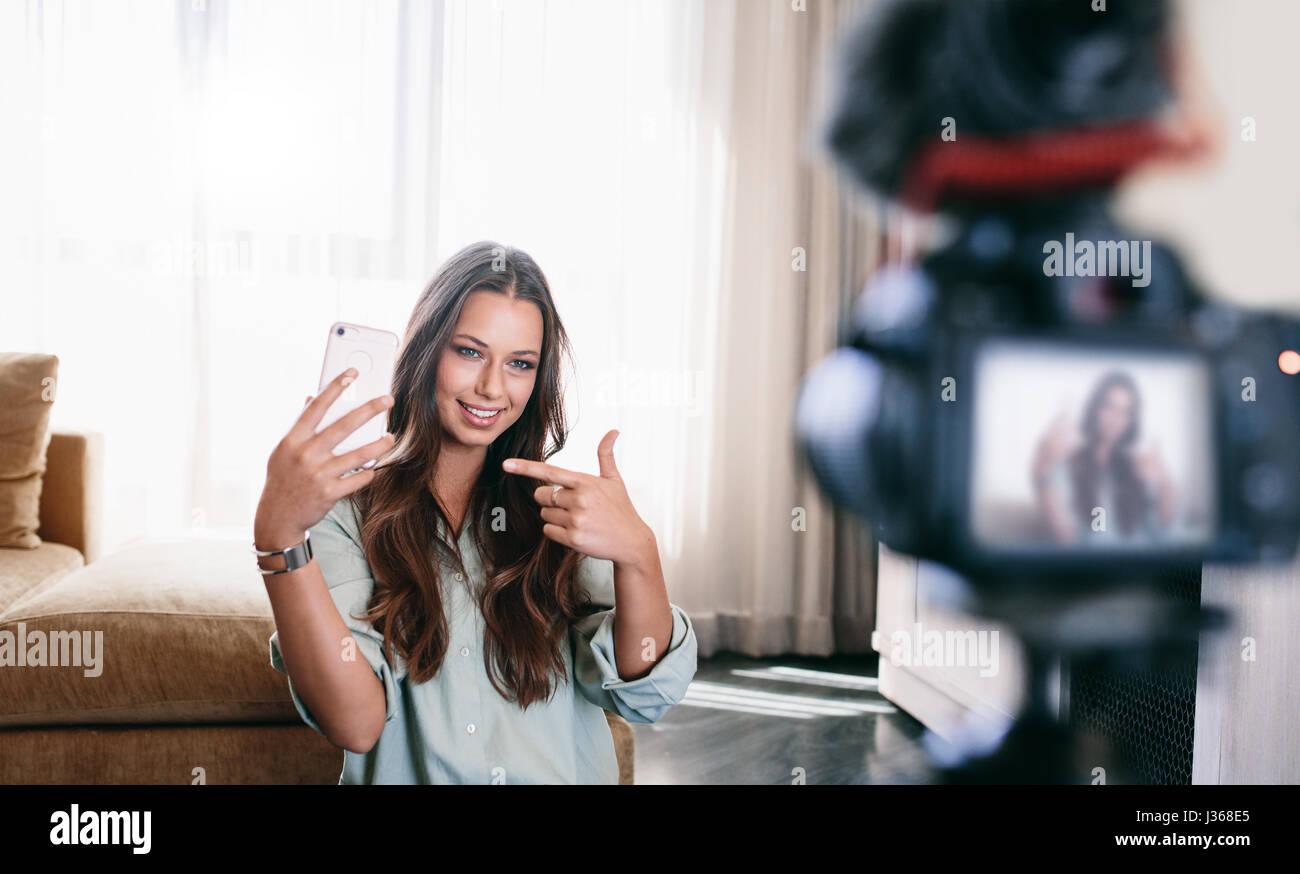 Azienda femmina smartphone, la registrazione di contenuti video per il suo blog. Giovani vlogger contenuto registrazione Immagini Stock