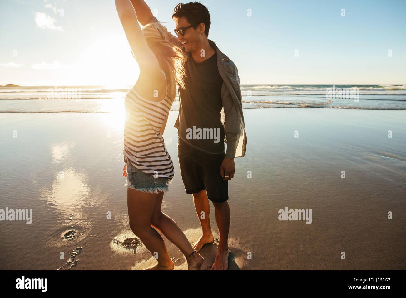 Colpo di amare giovane coppia danzante sulla spiaggia un giorno d'estate. Giovane uomo e donna ballare in riva Immagini Stock