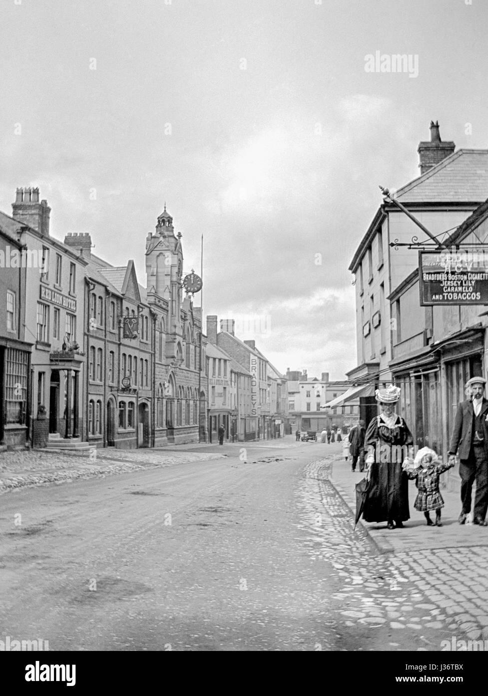 Guardando verso il basso una strada larga in Inghilterra vittoriana, una coppia con un bambino piccolo veglia sul Immagini Stock