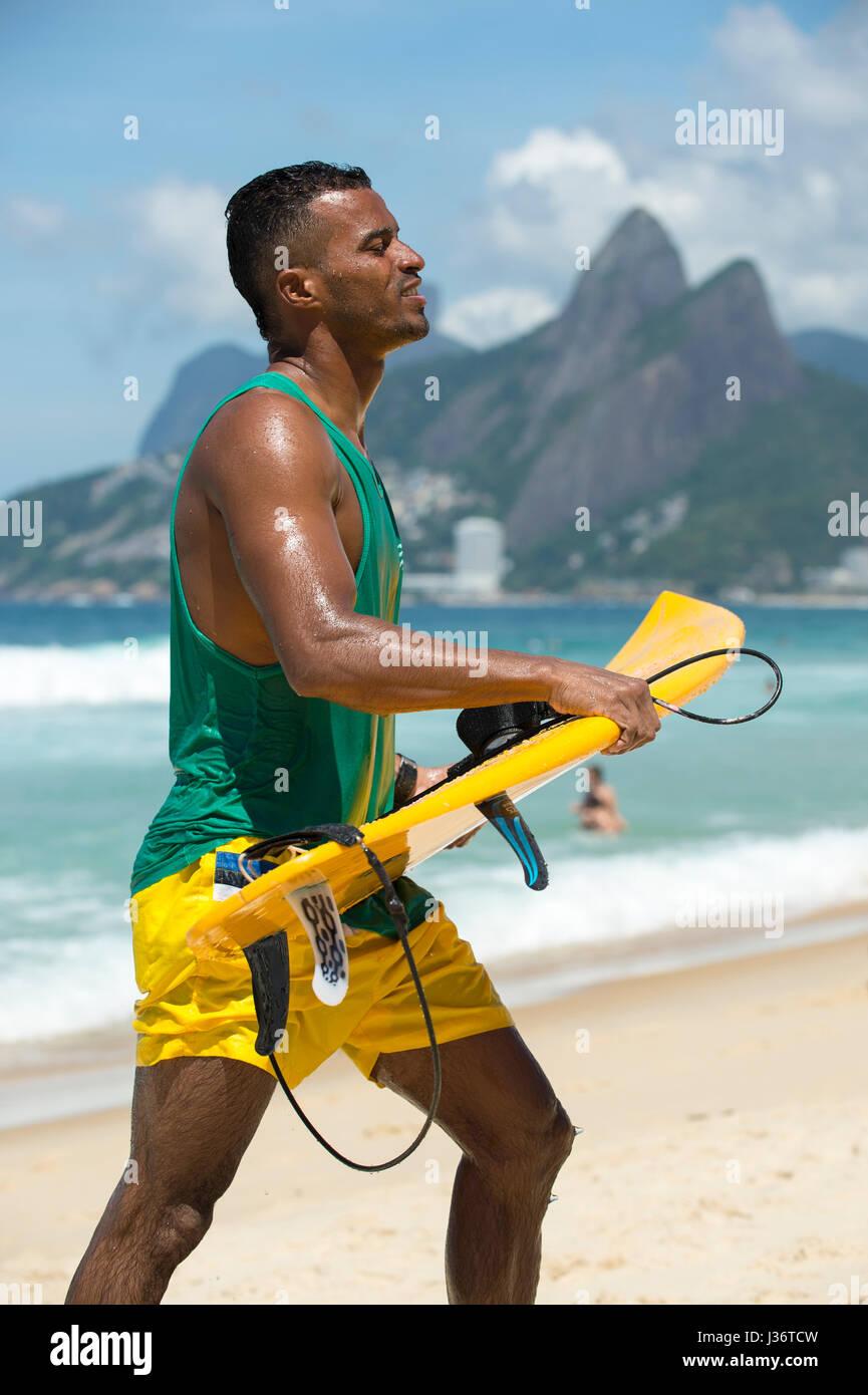 RIO DE JANEIRO - Febbraio 6, 2017: giovane brasiliano surfer cammina con la sua tavola da surf lungo il litorale Immagini Stock