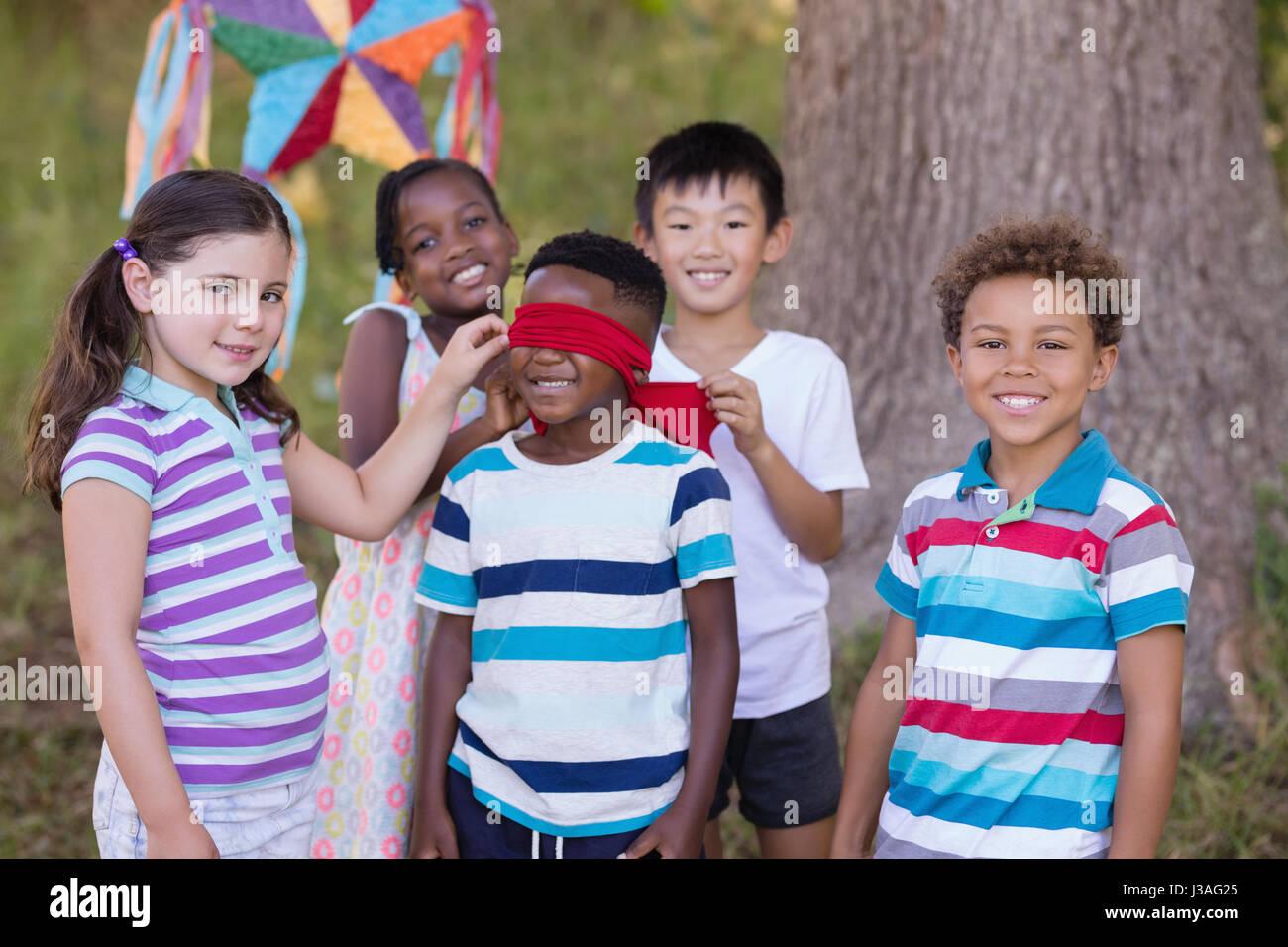 Ritratto di amici in piedi intorno a occhi bendati ragazzo in campeggio Immagini Stock