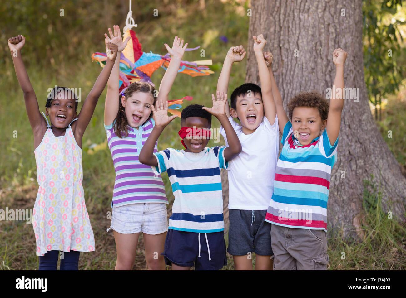 Happy amici tifo con gli occhi bendati ragazzo in campeggio Immagini Stock