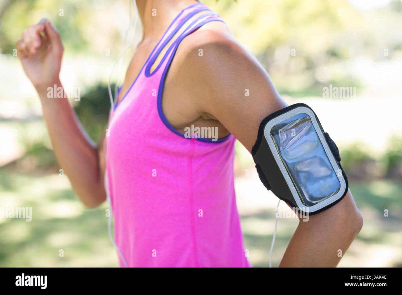 La sezione centrale del pareggiatore femmina con fascia braccio jogging nel parco Foto Stock