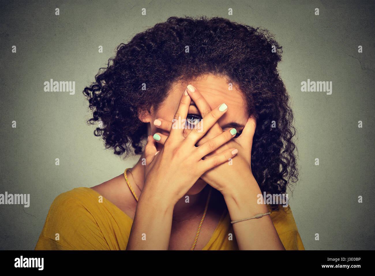Closeup donna timida nascondendo la faccia timida. Carino giovane donna caucasica peeking sebbene le mani. Sfondo Immagini Stock